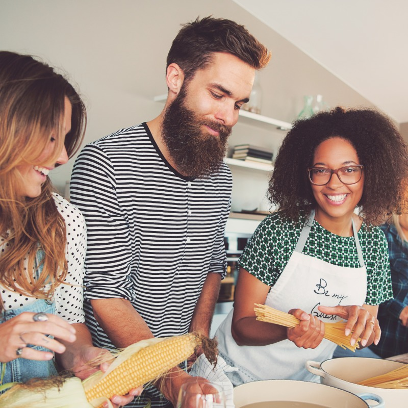 Three young people preparing meal together